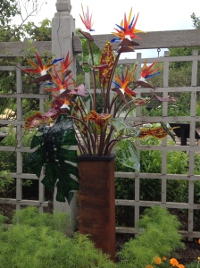 Tropical Splendor~ bird of paradise plant surrounded by croton leaves.